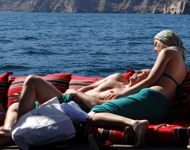 Dos turistas descansan en el dhow, tomando el  sol.