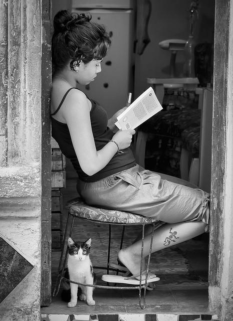 Gatito junto a chica leyendo, Foto tomada en La Habana por Howard Ignatius